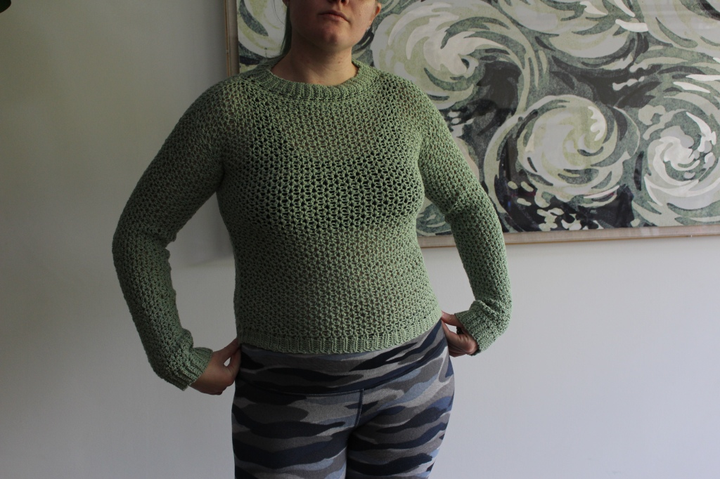 A woman wears a green crocheted sweater and blue camouflage leggings standing in front of a green and white wave painting on a white wall.