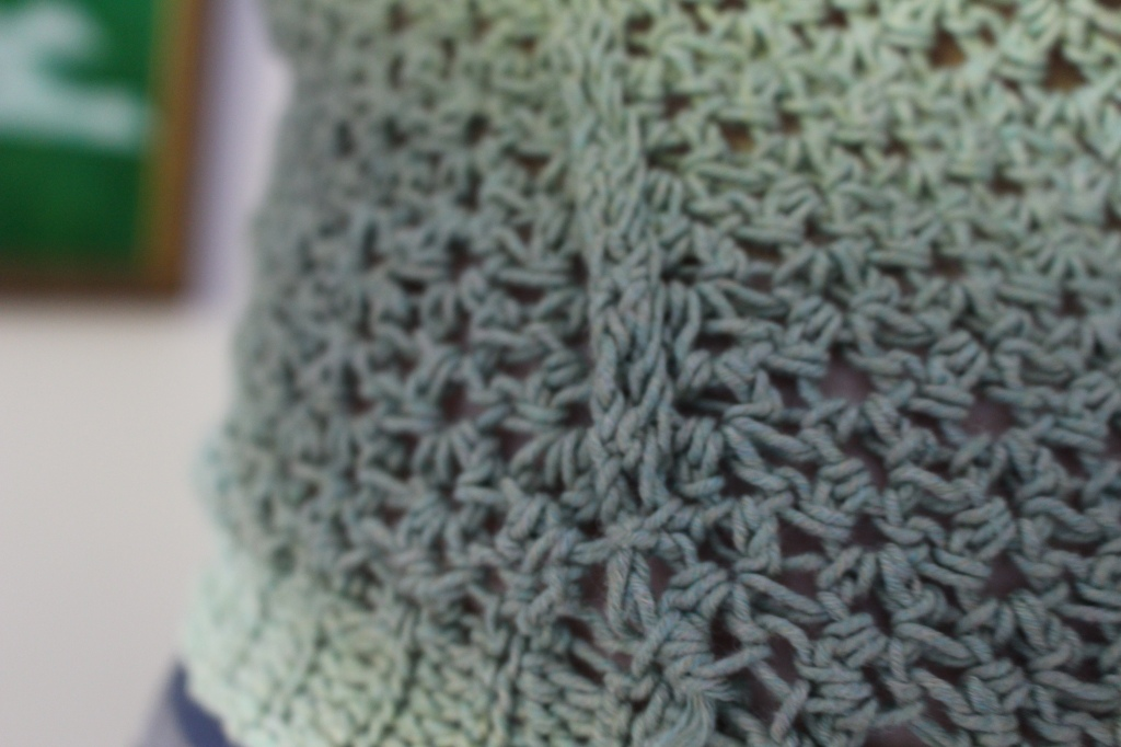 Close up of the side seam detail of a green crochet sweater near the bottom edge ribbing.