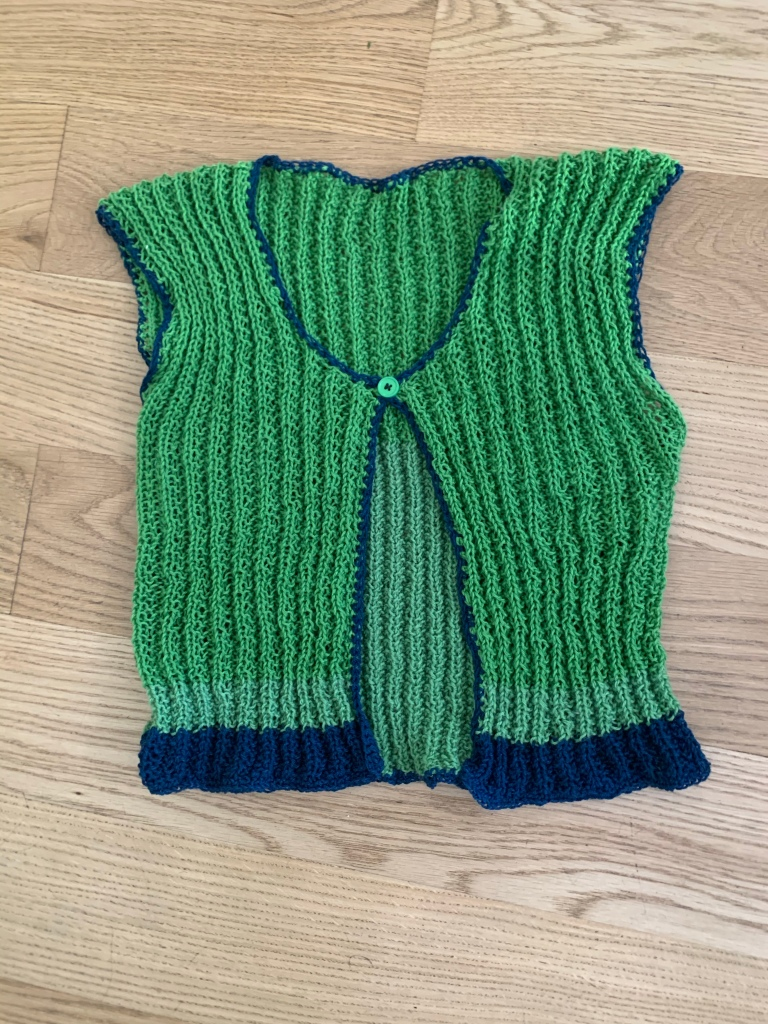 The front of a green knit vest with blue hem and crochet edging and a single green button at the center neck laying on a light wood floor.