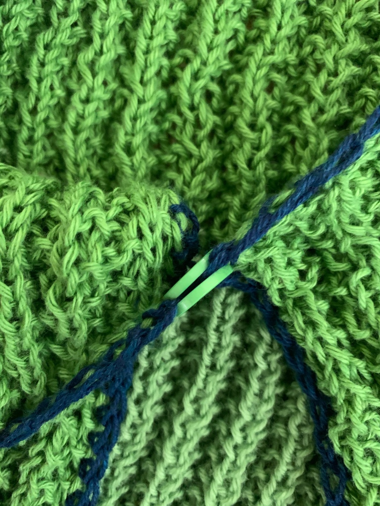 Close up of two buttons sewn together on the edge of a green knit vest with blue crochet edging.