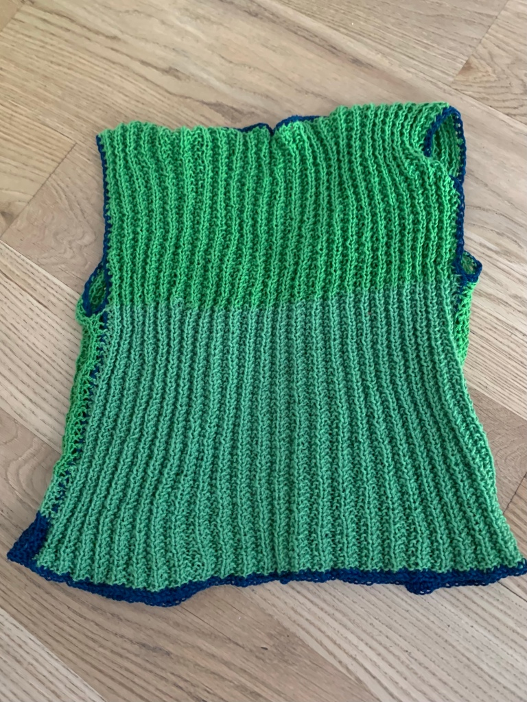 The back of a green knit vest with blue crochet edging laying on a light wood floor.