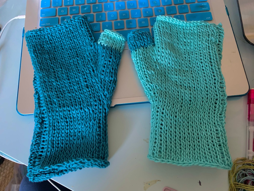 A pair of blue Tunisian crocheted gloves lay on a laptop keyboard. One is dark blue with a light blue thumb and the other is light blue with a dark blue thumb.
