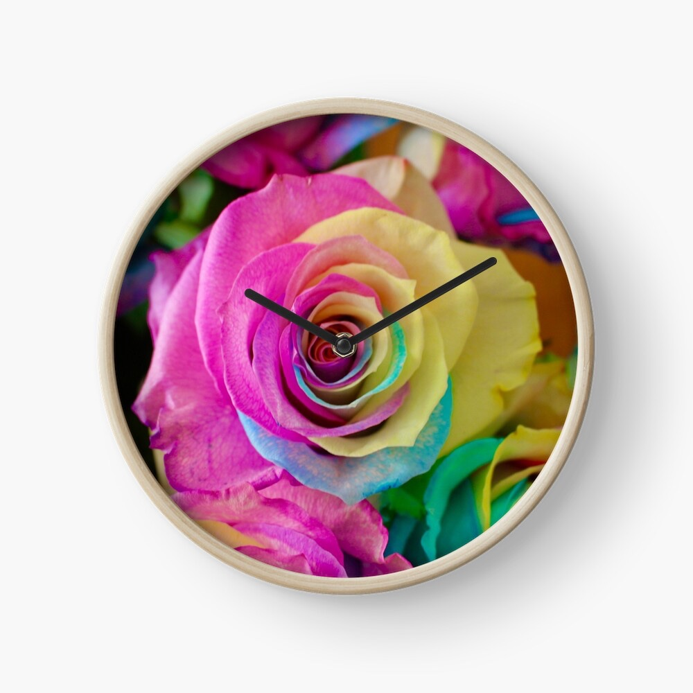 A clock with black hands printed with rainbow petalled roses on the face.